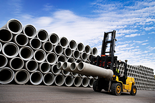 forklift driver in front of concrete pipes