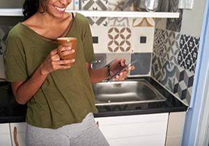 Smiling young woman drinking coffee and checking water bill on her phone