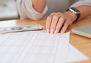 Hands of senior woman checking her bills